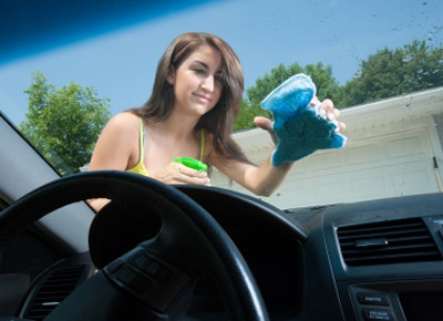 Girl cleaning car window