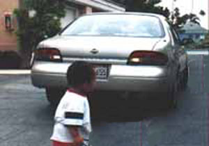 Car backing up, child